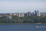 Apartment Complexes in The Bronx stand tall behind the Hudson River as a speed boat zips by.