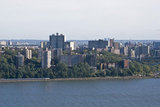 Apartment Complexes in The Bronx stand tall behind the Hudson River as a Metro-North train speeds by.
