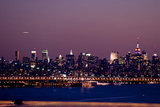 Manhattan becomes illuminated as night sets in behind the George Washington Bridge