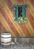 Window with shutters, flowers and diagonal siding with old wooden barrel