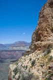 The Grand Canyon Opens up behind a rock formation.